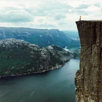L'uomo con una giacca gialla pone sulla sommità della roccia