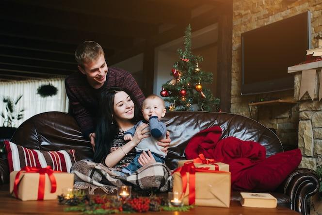 L'uomo guardando la moglie mentre lei tiene il suo bambino in braccio