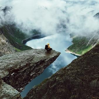 L'uomo si siede alla fine di trolltunga prima delle montagne