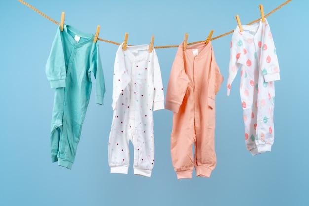 L'abbigliamento variopinto del bambino sveglio appende su una corda