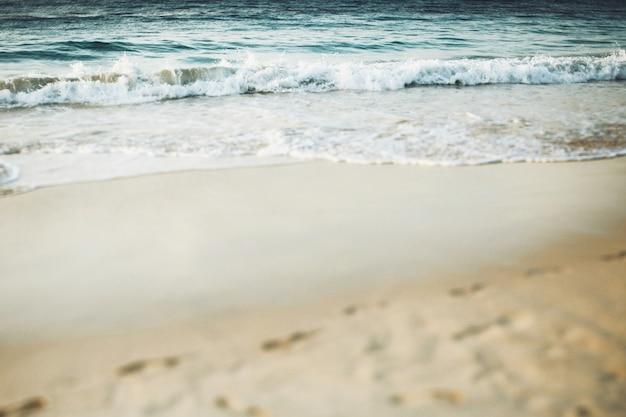 L'acqua blu spruzza sulla spiaggia sabbiosa