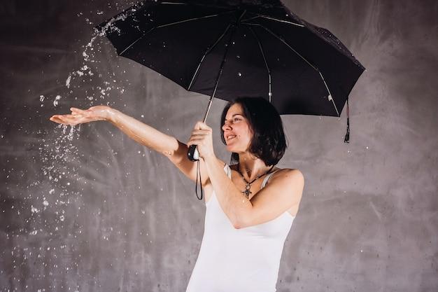 L'acqua cade sopra la donna sotto l'ombrello nero