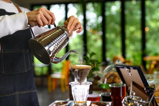 L'acqua calda della ragazza della donna del barista prepara il caffè filtrato dalla teiera d'argento al bello gocciolatore cromato trasparente su pesi semplici bianchi. vapore