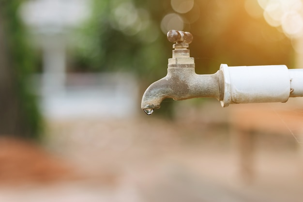 L'acqua che scorre dal vecchio rubinetto arrugginito con sfocatura verde i precedenti del parco in all'aperto
