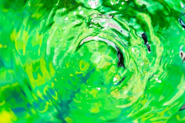 L'acqua del primo piano suona su una superficie verde dello stagno