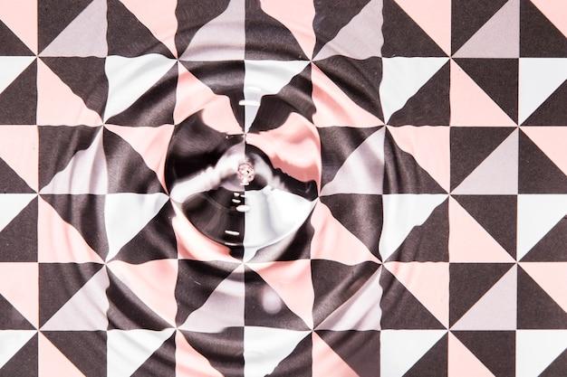 L'acqua del primo piano suona sulla poli superficie geometrica astratta dello stagno