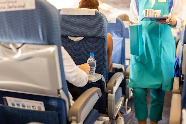 L'acqua della bottiglia selezionata di messa a fuoco con assistente di volo serve la bevanda ai passeggeri a bordo.