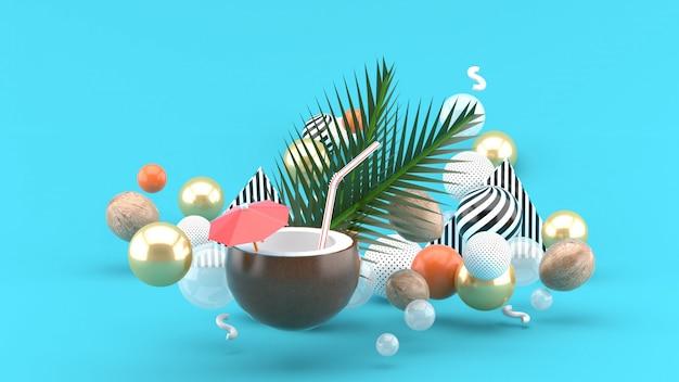 L'acqua di cocco e la noce di cocco sono tra le palline colorate sul blu. rendering 3d.