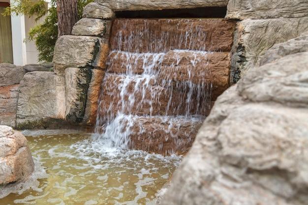 L'acqua limpida scorre attraverso una cascata artificiale a cascata