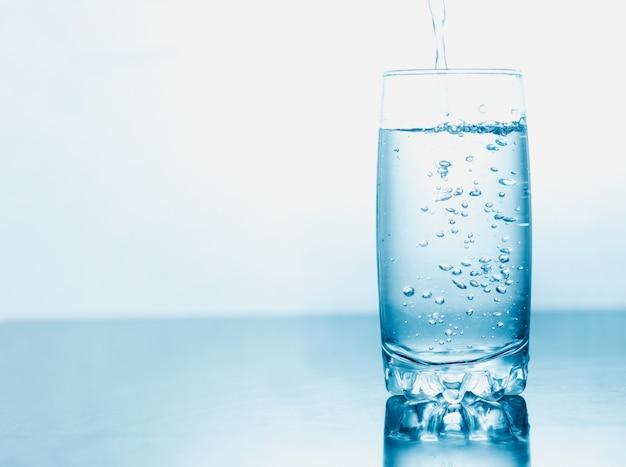 L'acqua potabile ha versato in un vetro isolato sopra fondo astratto blu. spazio per il testo