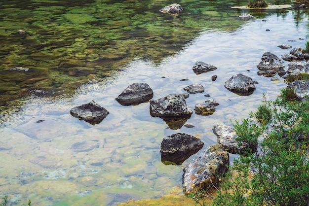 L'acqua pulita calma con le pietre si chiude su