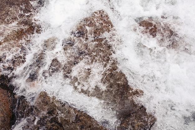 L'acqua schizza contro le rocce sul fiume