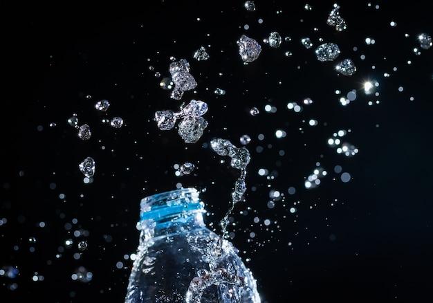 L'acqua schizza dalla bottiglia su sfondo nero