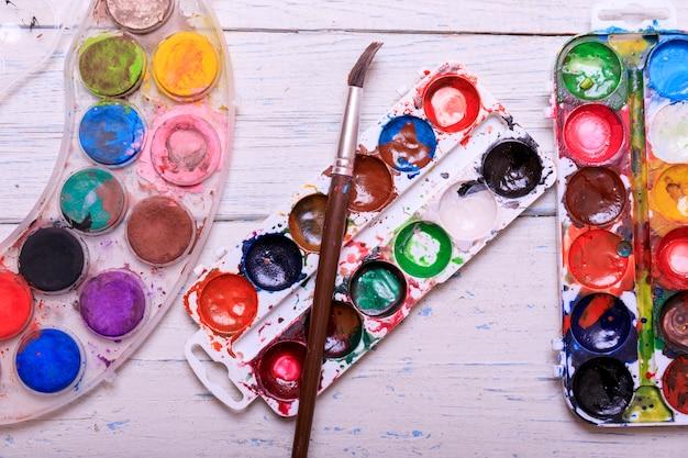 L'acquerello professionale dell'acquerello dipinge in scatola con le spazzole sul bordo di legno bianco anziano