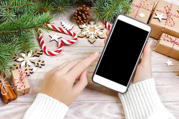 L'acquirente femminile effettua l'ordine sullo schermo dello smartphone