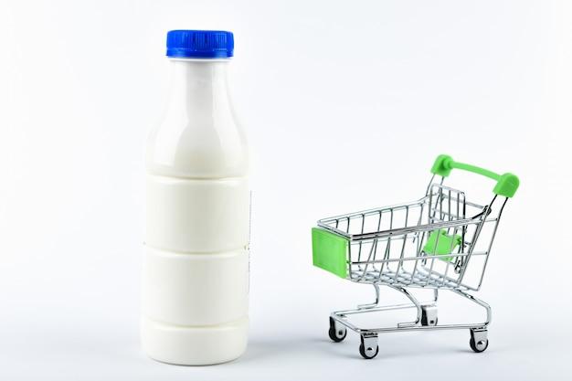 L'acquisto di latte concetto commerciale. acquista online. cestino e latte su un bianco. concetto di mangiare sano concetto di business