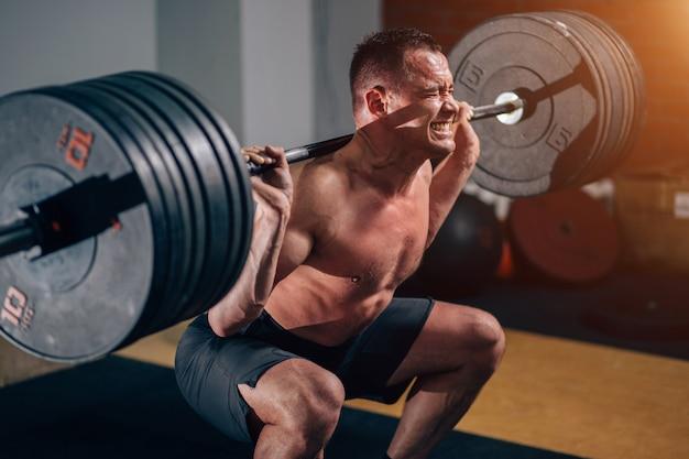 L'addestramento muscolare dell'uomo occupa con i bilancieri sulle spalle