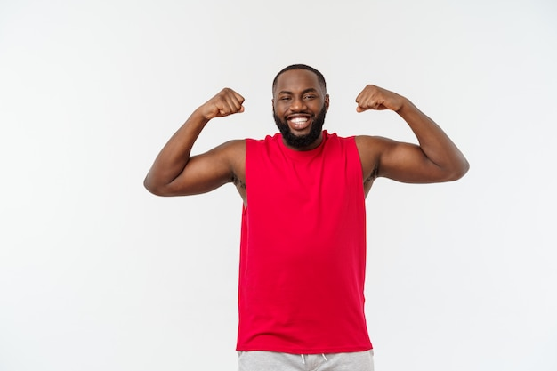 L'adolescente afroamericano mostra i muscoli sul braccio, isolato su bianco, ritratto dello studio, concetto di transizione di età
