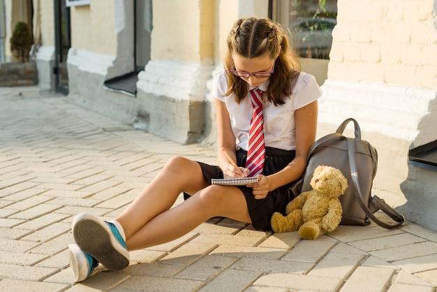 L'adolescente della scolara scrive in un taccuino. diario ragazze, segreti, primo amore