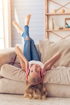 L'adolescente grazioso in cuffie sta ascoltando musica.