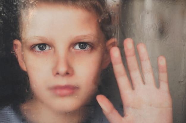 L'adolescente guarda fuori dalla finestra. gocce di pioggia sulla finestra.