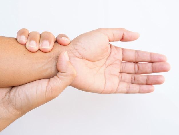 L'adulto asiatico che soffre di dolore al polso, usa il tocco della mano sul braccio e massaggia il polso per alleviare, parte del corpo isolata sulla superficie bianca.
