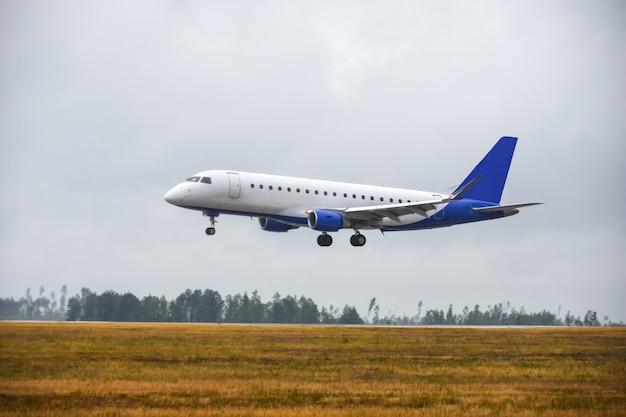 L'aereo di linea del passeggero è atterrato sulla pista dell'aeroporto in caso di maltempo con la pioggia
