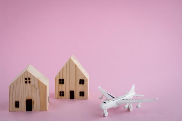 L'aeroplano bianco e la casa di legno modellano su fondo rosa per il concetto di viaggio