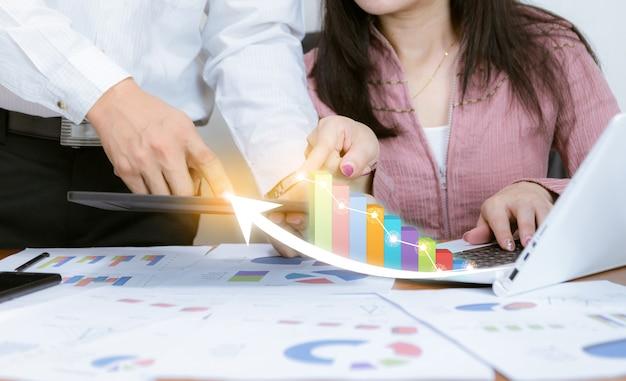 L'affare analizza i grafici con lo sviluppo della tecnologia che indica il grafico corporativo il successo e il concetto di piano crescente