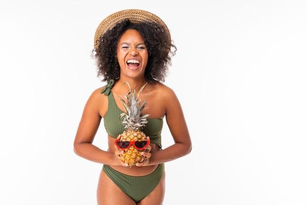 L'africano in un costume da bagno verde tiene un ananas con i vetri su bianco