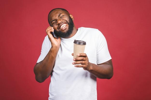L'afroamericano felice bello con il telefono mobile e porta via