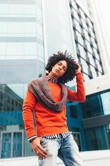 L'afroamericano nero riccio vestito alla moda giovane con gli occhiali cammina attraverso le vie