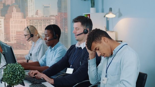 L'agente del call center multirazziale si sente esausto e distrutto.