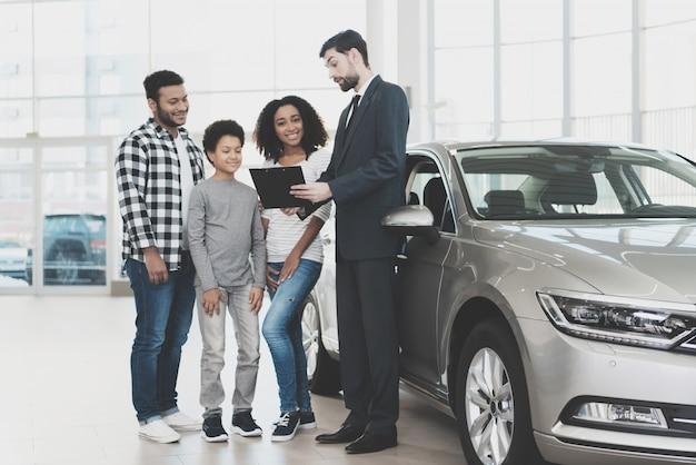 L'agente di contratto automobilistico di firma della famiglia offre il credito.