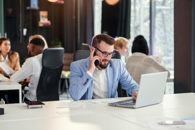L'agente di vendita professionale lavora su un computer portatile e si consulta sul cellulare con il suo socio in un moderno centro di co-working.