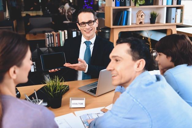 L'agente immobiliare mostra la famiglia sul tablet di pianificazione domestica.