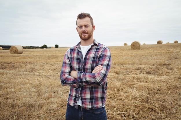 L'agricoltore che sta con le armi ha attraversato nel campo