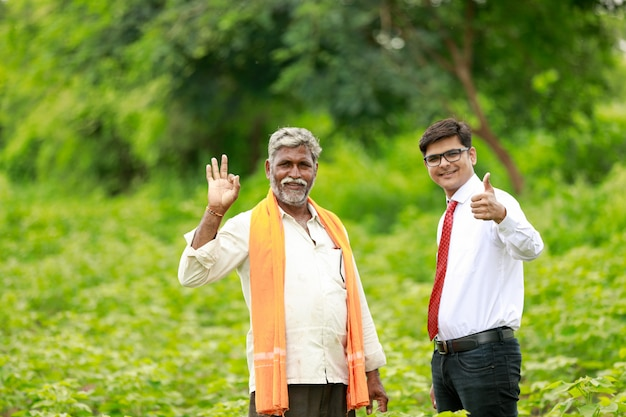 L'agricoltore e l'agronomo indiano che mostrano i colpi su nel campo verde del cotone