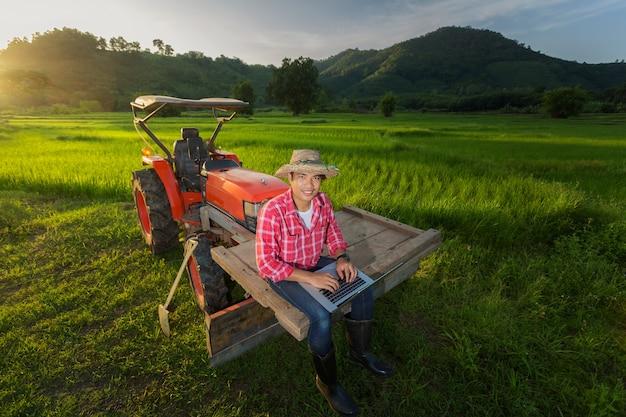 L'agricoltore ha registrato una crescita della produttività seduto su un trattore sullo sfondo una risaia