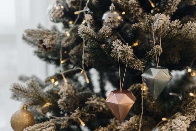 L'albero di natale artificiale in un interno luminoso con i fiori d'argento nevica sui rami. natale.
