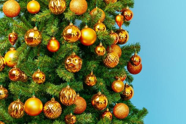 L'albero di natale con le bagattelle dorate si chiude su sul blu