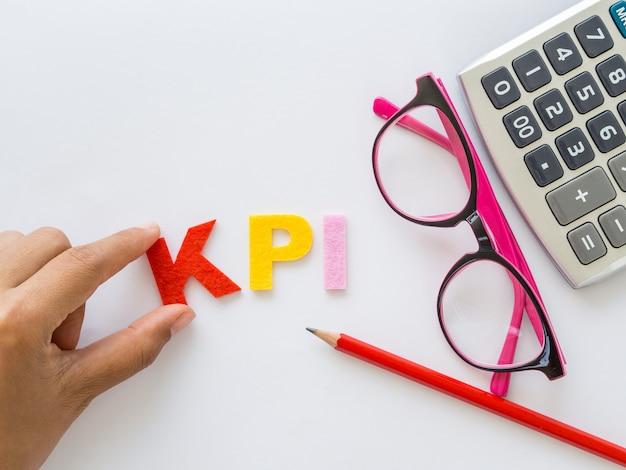 L'alfabeto di kpi con la matita rossa e vetri rosa ha messo sopra il fondo bianco della tavola