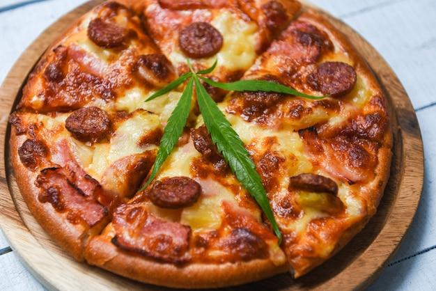 L'alimento della cannabis withpizza sul vassoio di legno e sulla vista superiore della foglia del basilico dei peperoncini rossi