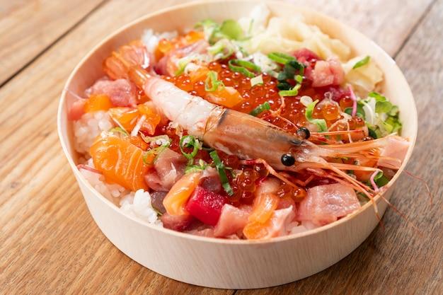 L'alimento giapponese di chirashi saporito e delizioso sul fondo di legno della tavola, il cibo sano e mangia bene il concetto. porta via il cibo a casa. avvicinamento