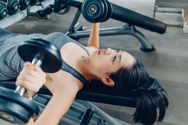 L'allenamento della donna per la panca del manubrio introduce la palestra di forma fisica.