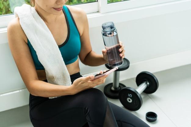 L'allenamento di esercizio della donna nella rottura di forma fisica della palestra si rilassa.