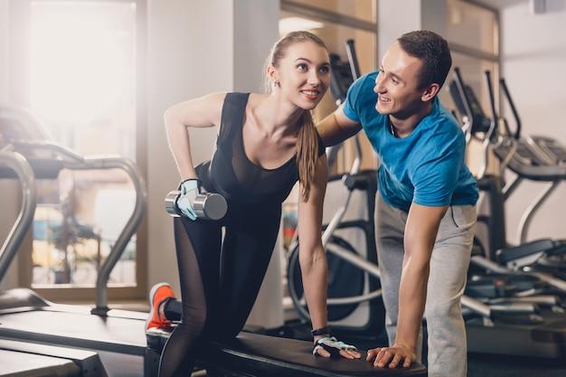 L'allenatore aiuta la ragazza a fare l'esercizio.