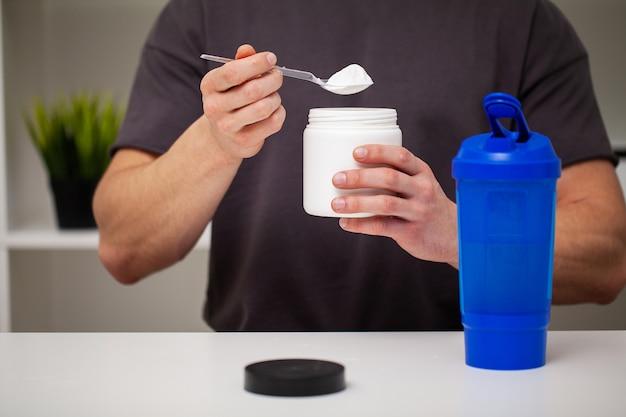 L'allenatore prepara un frullato di proteine nello shaker dopo l'allenamento