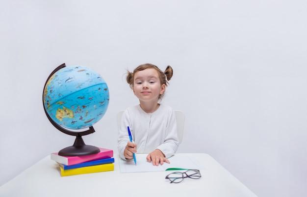 L'allievo curioso della ragazza si siede ad una tabella con un taccuino e una penna e esamina la macchina fotografica su un bianco isolato