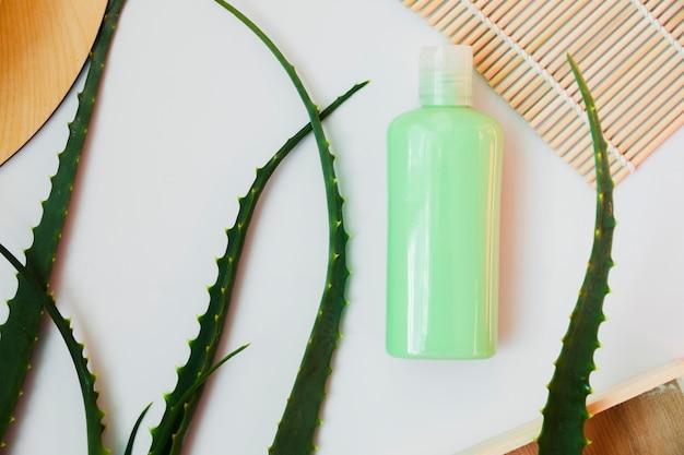 L'aloe vera lascia con una bottiglia di crema di bellezza